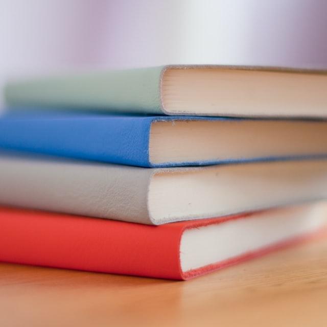 Fyra färgglada böcker på ett bord